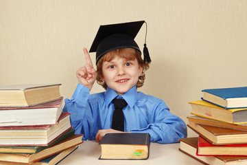 Young smiling boy in academic hat among the old books