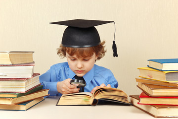 Serious boy in academic hat reading books with magnifying glass