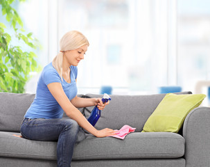 Housewife cleaning a couch with a rag