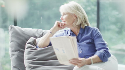 Attractive mature woman relaxing at home alone reading a newspaper