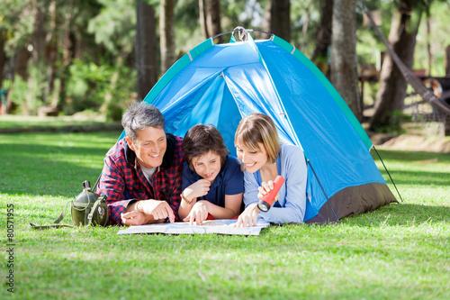Leinwanddruck Bild Family Reading Map At Campsite