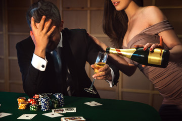 dramatic photo loser poker man and lady pours him a glass of cha