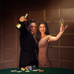 Beautiful couple celebrating victory in poker game