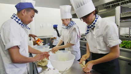 Chefs in a restaurant or bakery kitchen preparing dough for bread or pastry