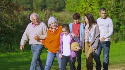 Happy extended family group walking in the countryside on an autumn day