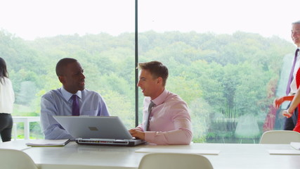 Two businessmen in discussion in contemporary glass office