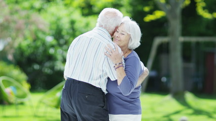 Romantic senior couple dancing together outdoors on a summer day