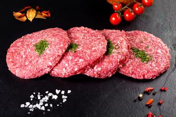 Carne cruda. hamburguesas de carniceria fondo negro y tomate