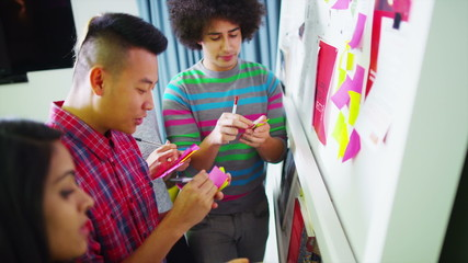 Young creative business team brainstorming with the use of post-it notes
