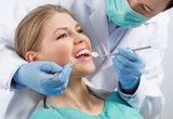 Gingivitis therapy. Male surgeon examining female's molar