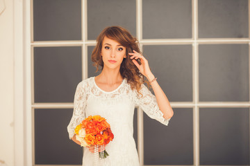 beautiful girl in a bright dress with a bouquet of flowers