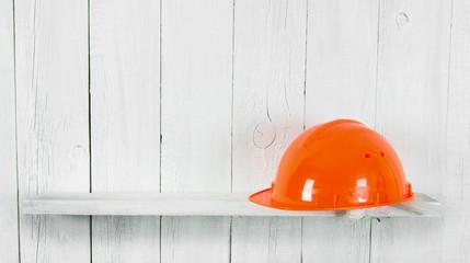 Helmet on a wooden shelf.