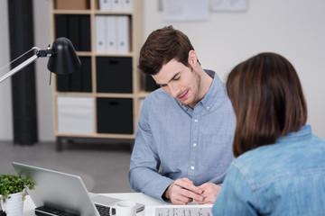 zwei kollegen sitzen am schreibtisch und reden über ein projekt
