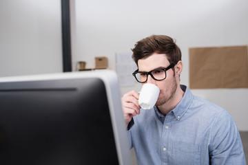 angestellter im büro schaut auf computer und trinkt kaffee