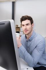 mitarbeiter sitzt am schreibtisch und schaut auf computer