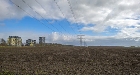 Power line in a plowed field near a city in spring
