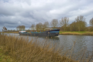 Barge sailing in a canal under a cloudy sky in spring