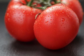 ripe washed tomatoes on vine on slate background