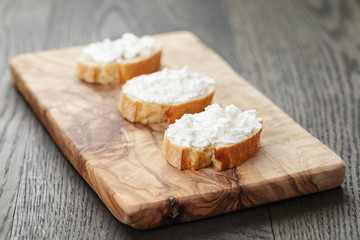 crunchy baguette slices with cream cheese on olive board