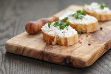 crunchy baguette slices with cream cheese and green onion on
