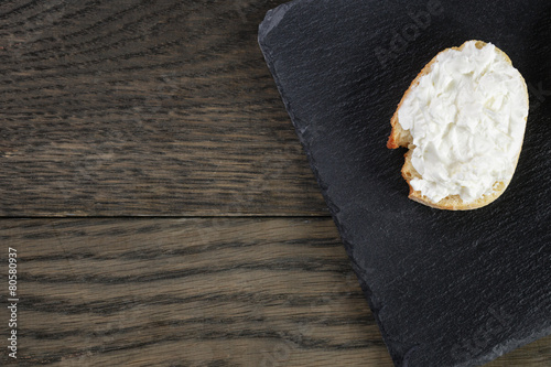 crunchy baguette slices with cream cheese on slate board - 80580937
