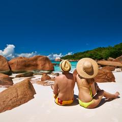 Couple sitting on a beach at Seychelles
