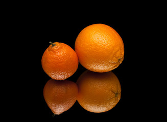 ripe orange and mandarin on a black background with reflection