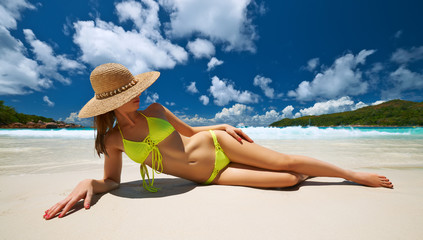 Woman in yellow bikini lying on beach at Seychelles
