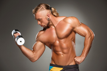 Attractive male body builder on gray background