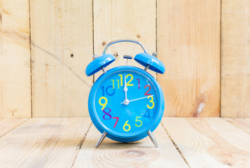 Alarm Clock isolated on white, in blue, showing twelve o'clock