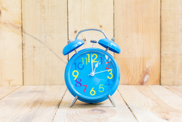 Alarm Clock isolated on white, in blue, showing one o'clock on w