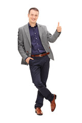 Young man leaning on a wall and giving thumb up