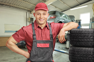 Mechanic leaning on a stack of tires in a garage