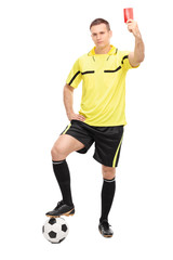 Strict football referee showing a red card