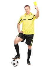 Young football referee showing a yellow card