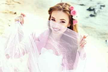 Beautiful young bride with pink roses on the beach