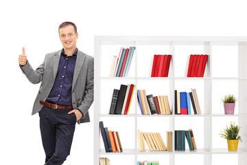 Guy leaning on a bookshelf and giving a thumb up