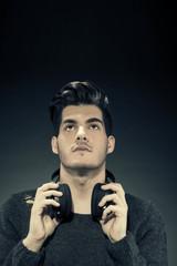Handsome guy with headphones over grey background