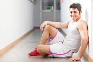Caucasian man in sportswear is sitting on the floor in corridor