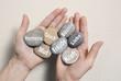 Hände halten Steine mit Glück, Mut, Kraft, Freude, Harmonie - 80589382