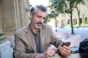 Mature man connected on smartphone at coffee shop