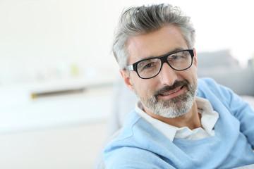 Smiling mature man with grey hair wearing eyeglasses