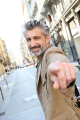 Handsome middle-aged man pointing finger at camera