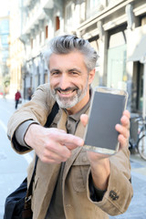 Cheerful mature man showing smartphone to camera
