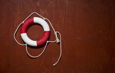 Red and white life buoy hanging on the side of a wood