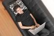 Mit dem Laptop auf dem Sofa