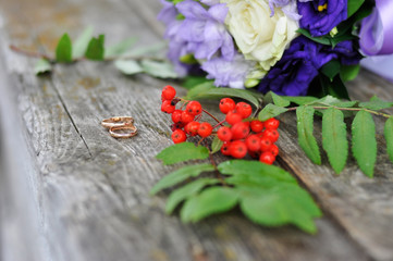Engagement rings and rowan on old wood