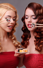 Two women eating sushi rolls