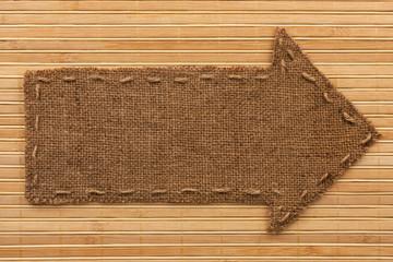 Arrow made of burlap lies on a bamboo mat
