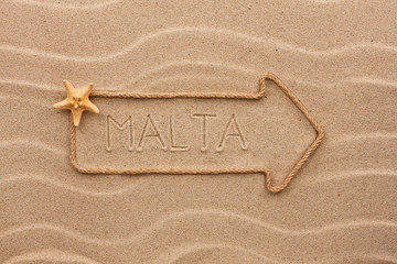 Arrow made of rope and starfish with the word Malta on the sand